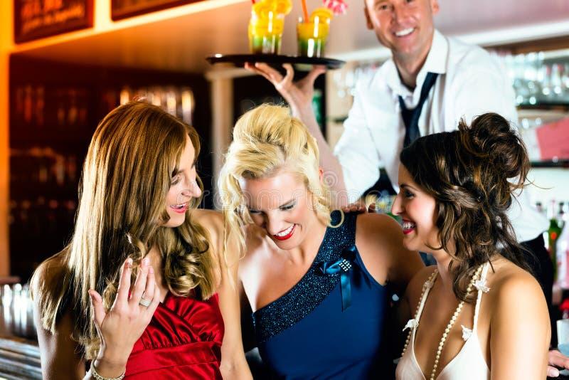 Jovens mulheres com os cocktail no clube ou na barra fotos de stock