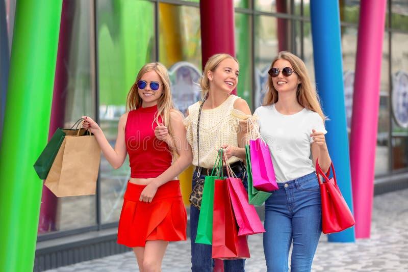Jovens mulheres com sacos de compras que andam na rua da cidade fotografia de stock royalty free