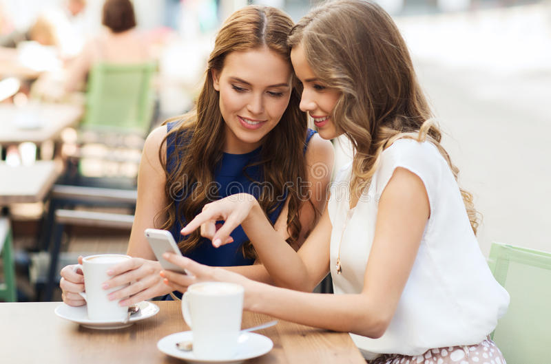 Jovens mulheres com smartphone e café no café imagens de stock royalty free