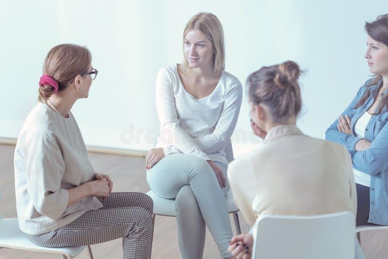Jovens mulheres de ajuda do terapeuta durante a reunião do grupo de apoio imagem de stock royalty free