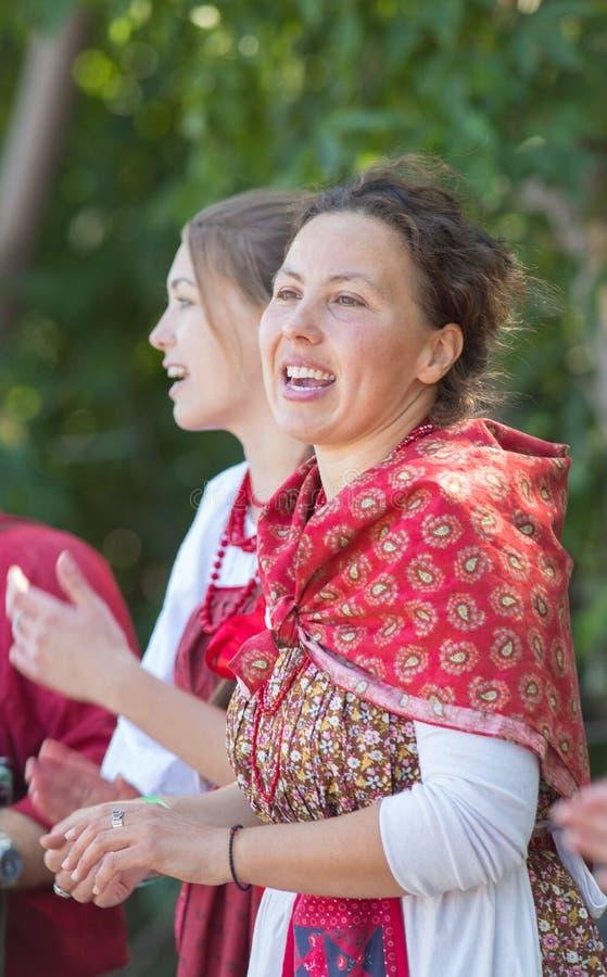 Jovens mulheres de sorriso em trajes populares do russo no fundo da árvore fotografia de stock