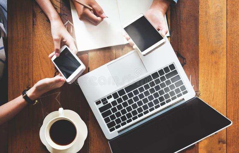 Jovens mulheres dos colegas de trabalho de trabalhos de equipa do negócio que trabalham no café com portátil, telefone celular co fotos de stock royalty free