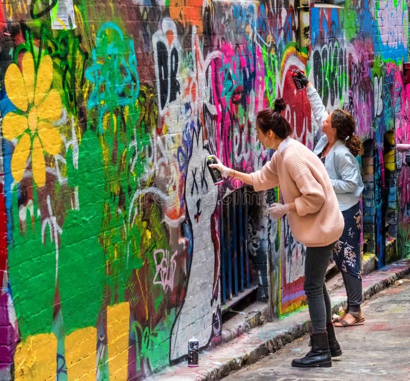 Jovens mulheres e grafittis imagem de stock