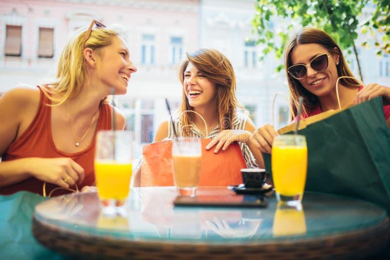 Jovens mulheres em um caf? ap?s uma compra fotos de stock royalty free