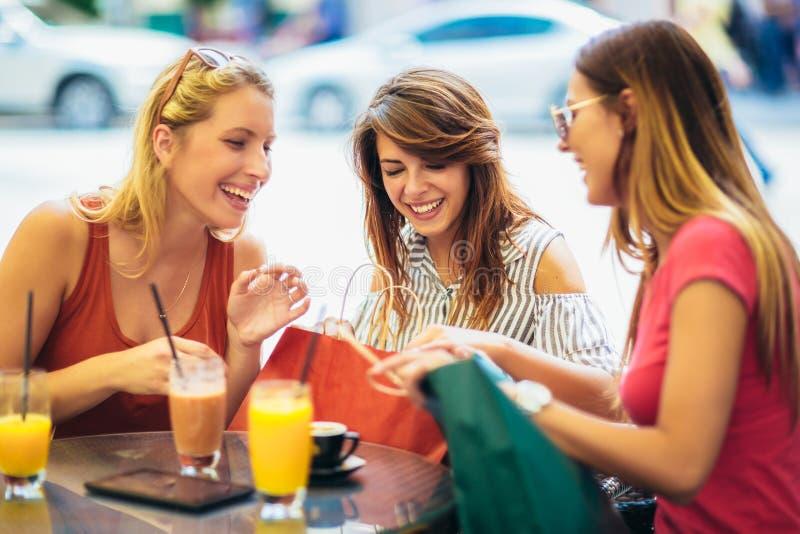 Jovens mulheres em um caf? ap?s uma compra fotos de stock
