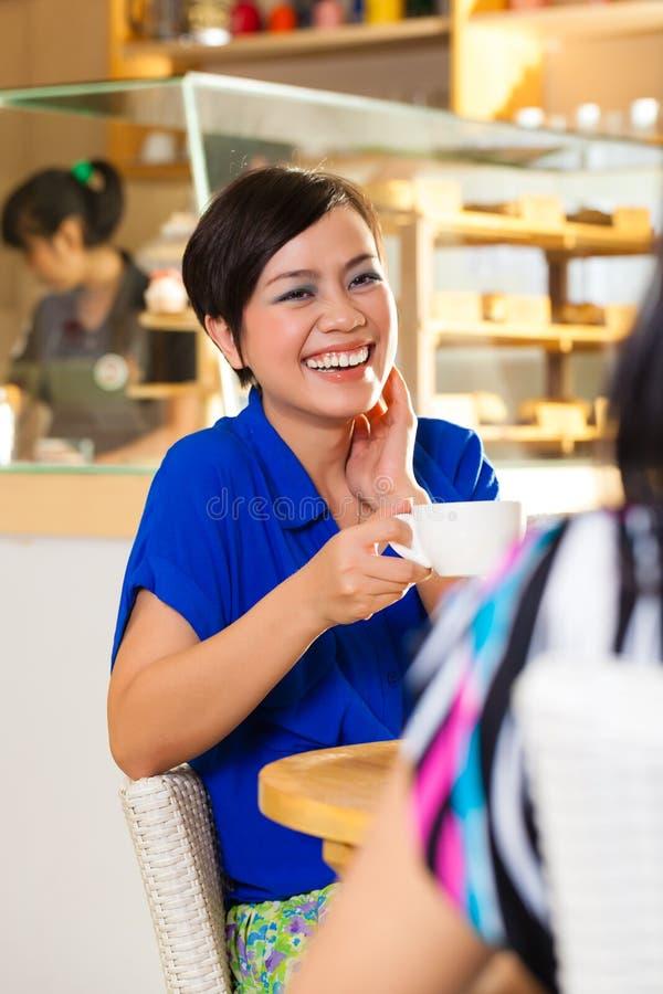 Jovens mulheres em uma cafetaria asiática fotos de stock