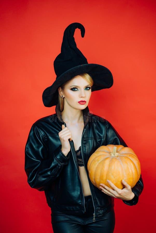 Jovens mulheres emocionais em trajes do Dia das Bruxas no partido sobre o fundo vermelho com ab?bora Conceito de Halloween fotos de stock royalty free