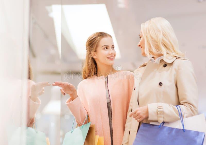 Jovens mulheres felizes com os sacos de compras na alameda imagens de stock royalty free