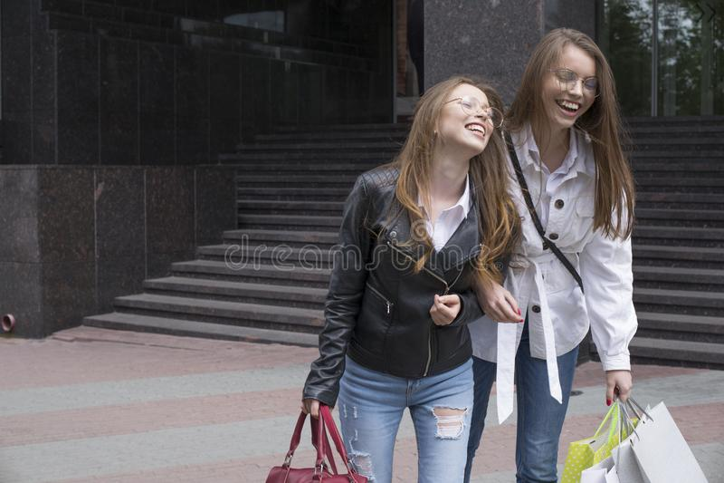 Jovens mulheres felizes com sacos de compras que andam ao longo da rua da cidade fotografia de stock royalty free