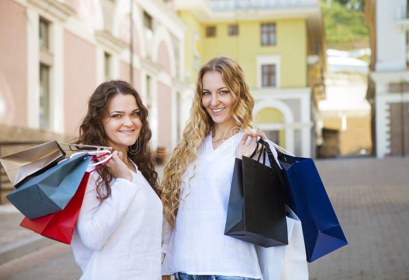 Jovens mulheres felizes com sacos de compras que andam na rua fotos de stock royalty free