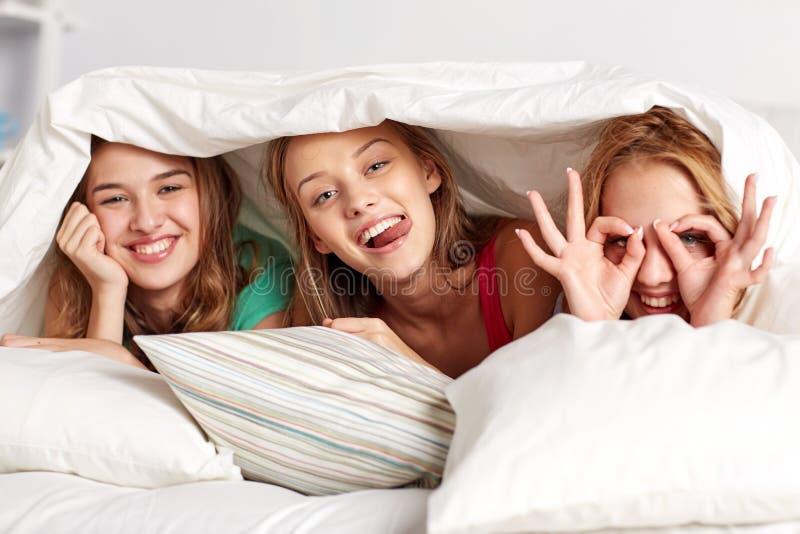 Jovens mulheres felizes no partido de pijama da cama em casa fotografia de stock