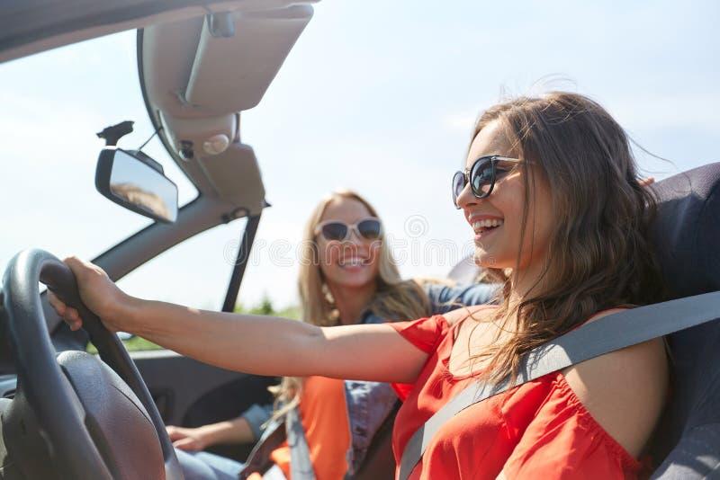 Jovens mulheres felizes que conduzem no carro do cabriolet fotografia de stock