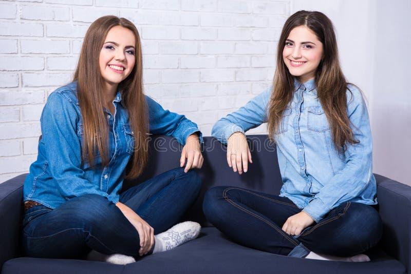 Jovens mulheres felizes que sentam-se no sofá na sala de visitas foto de stock