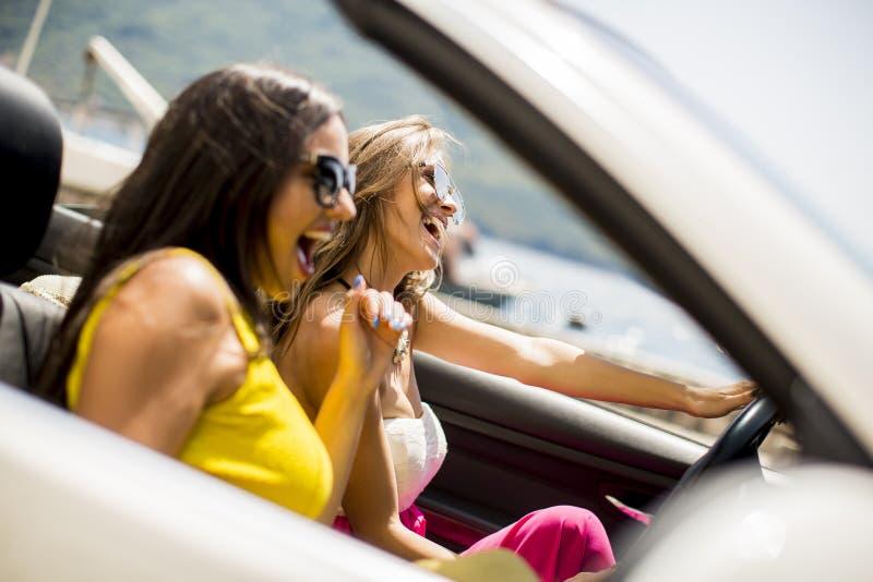 Jovens mulheres na condução de carro branca do cabriolet em toda parte e no lookin imagens de stock