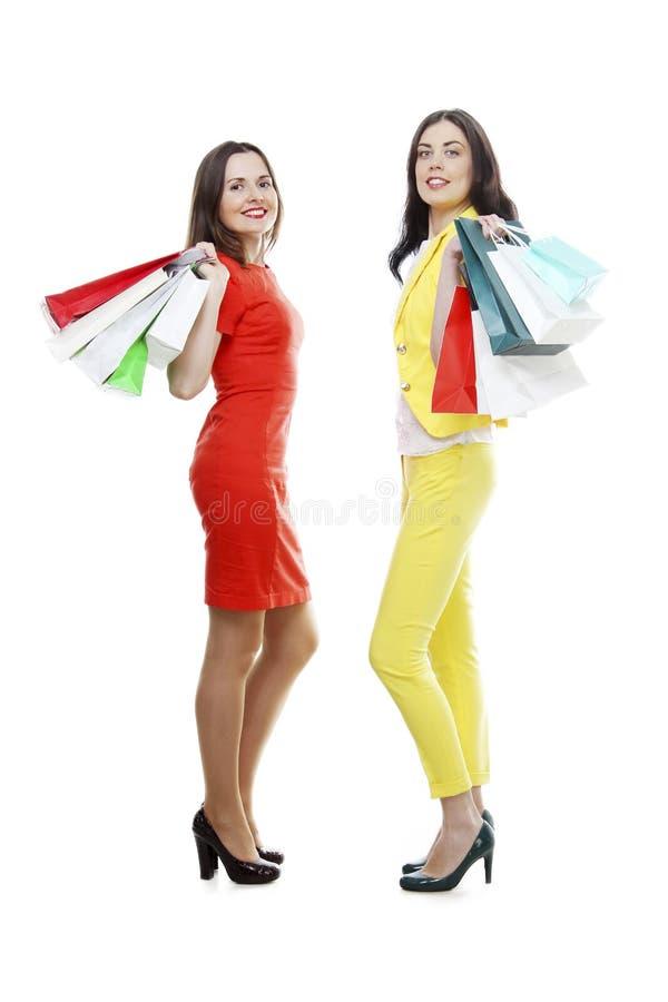 Jovens mulheres na roupa vermelha e amarela com os sacos de compras isolados no branco imagem de stock