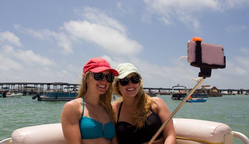 Jovens mulheres no barco que toma Selfie foto de stock