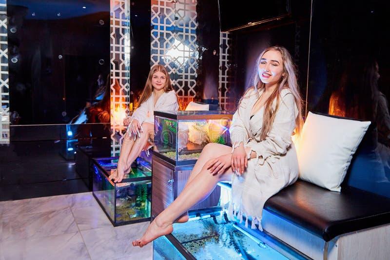 Jovens mulheres no sal?o de beleza Pedicure e tratamento de mãos dos peixes no tratamento moderno novo dos termas com luz bonita fotos de stock royalty free