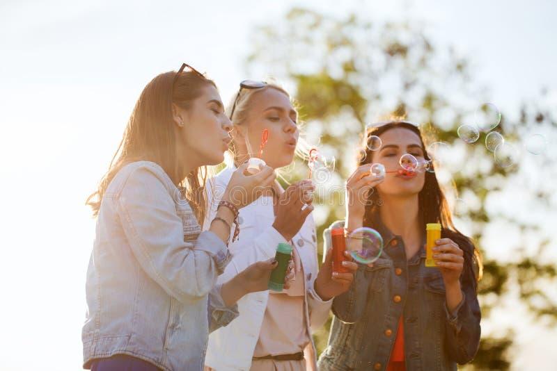 Jovens mulheres ou meninas que fundem bolhas fora foto de stock