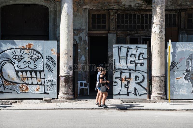 Jovens mulheres que andam na frente dos grafittis e do architectur colonial mórbido, Havana, Cuba imagens de stock