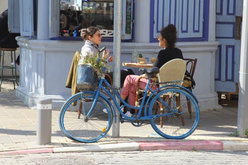 Jovens mulheres que bebem o terraço na moda de fala, Tel Aviv, Israel foto de stock