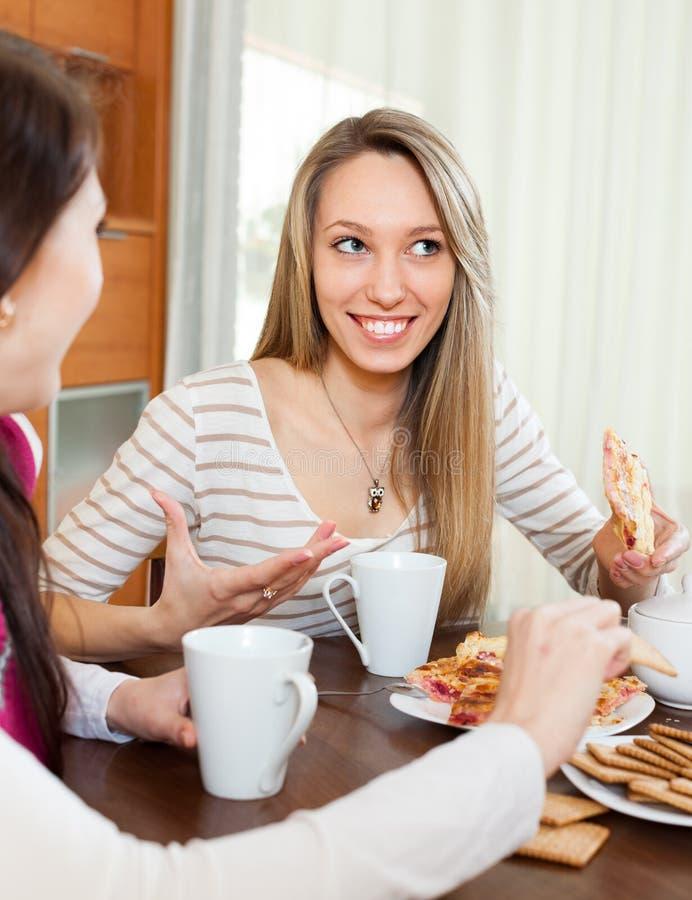 Jovens mulheres que bisbilhotam e que bebem o chá fotos de stock