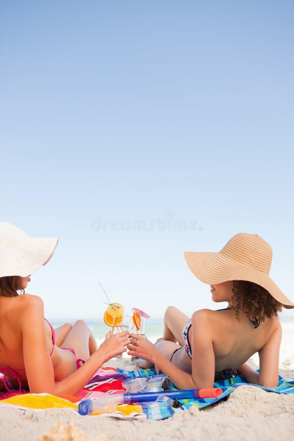 Jovens mulheres que clinking seus vidros ao olhar se imagem de stock