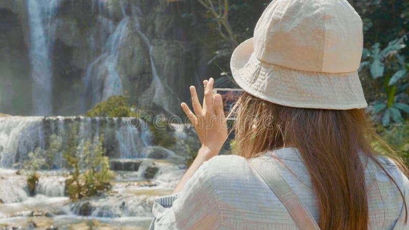 Jovens mulheres que estão contra a cachoeira e que tomam a foto no telefone esperto foto de stock royalty free