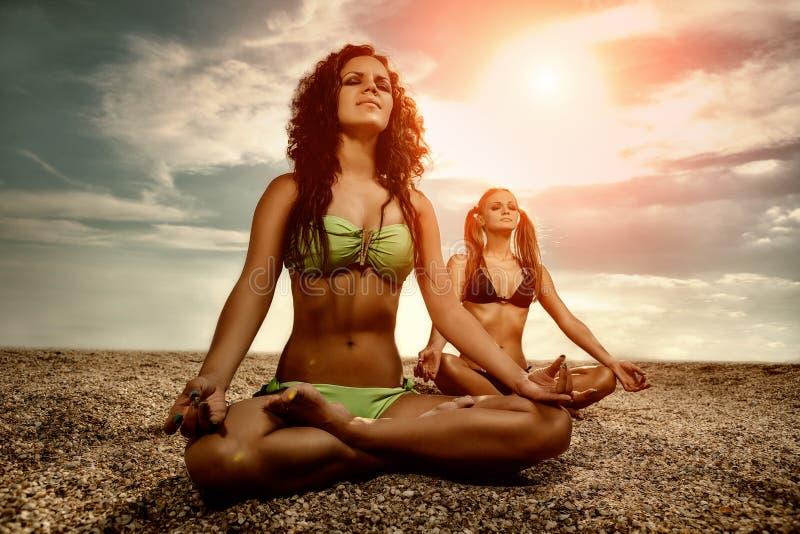Jovens mulheres que fazem a ioga na praia fotos de stock royalty free