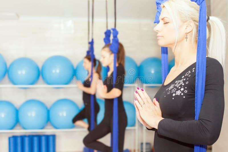Jovens mulheres que fazem o exercício aéreo da ioga ou a ioga antigravitante foto de stock