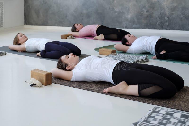 Jovens mulheres que fazem o exercício da ioga, encontrando-se na pose de reclinação do herói, Supta Virasana foto de stock royalty free