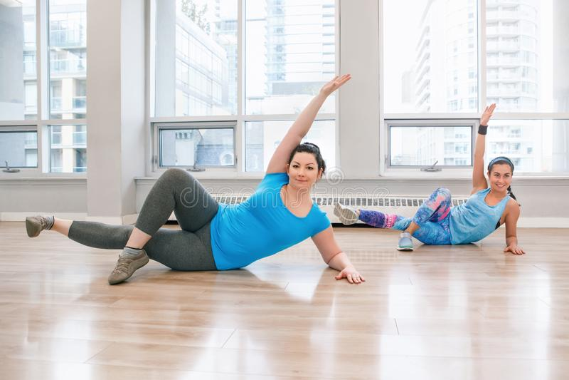 Jovens mulheres que fazem o exercício na classe do gym dentro para afrouxar o peso imagem de stock royalty free