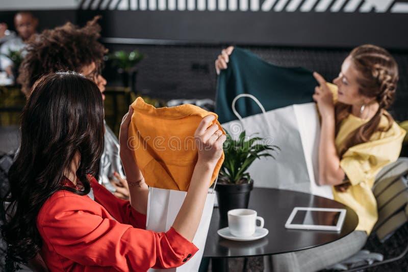 jovens mulheres que mostram seus vestidos novos entre si foto de stock