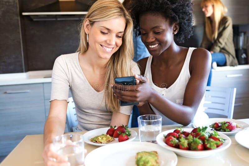 Jovens mulheres que olham seu telefone celular ao ter o almoço com amigos em casa foto de stock royalty free