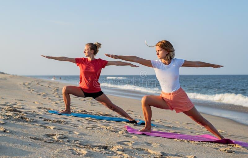 Jovens mulheres que praticam a ioga na praia Meninas bonitas que fazem a ioga que está na pose do guerreiro fotografia de stock royalty free