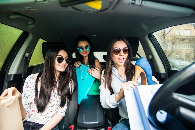 Jovens mulheres que retornam da compra dentro do carro Moças que montam o carro e que retornam da compra foto de stock
