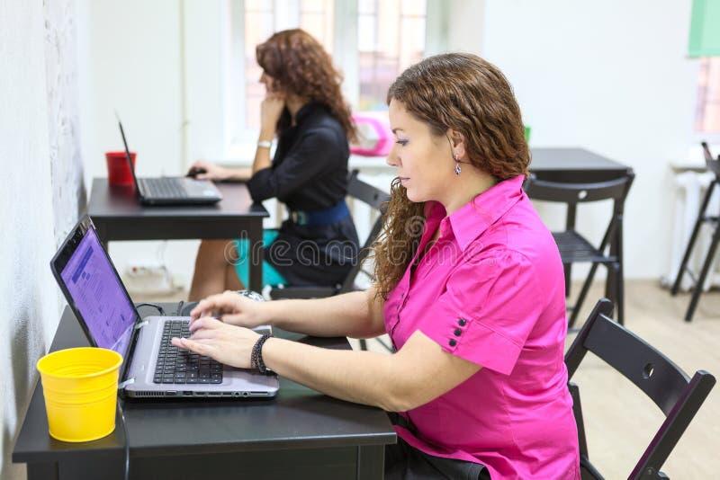Jovens mulheres que trabalham com os portáteis em mesas fotografia de stock royalty free