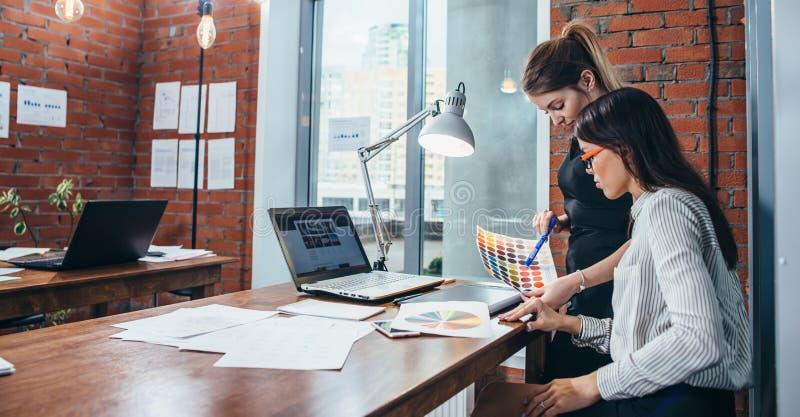 Jovens mulheres que trabalham em um design web novo usando amostras de folha da cor e nos esboços que sentam-se na mesa no escrit imagem de stock
