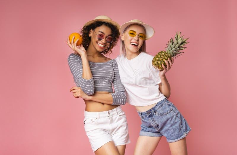Jovens mulheres saudáveis que levantam com laranja e o abacaxi frescos imagens de stock royalty free