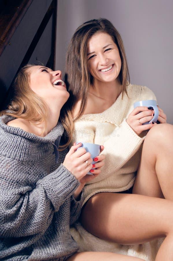2 jovens mulheres 'sexy' bonitas que sentam-se em uma camiseta de confecção de malhas em um chá bebendo geral que ri olhando o re foto de stock