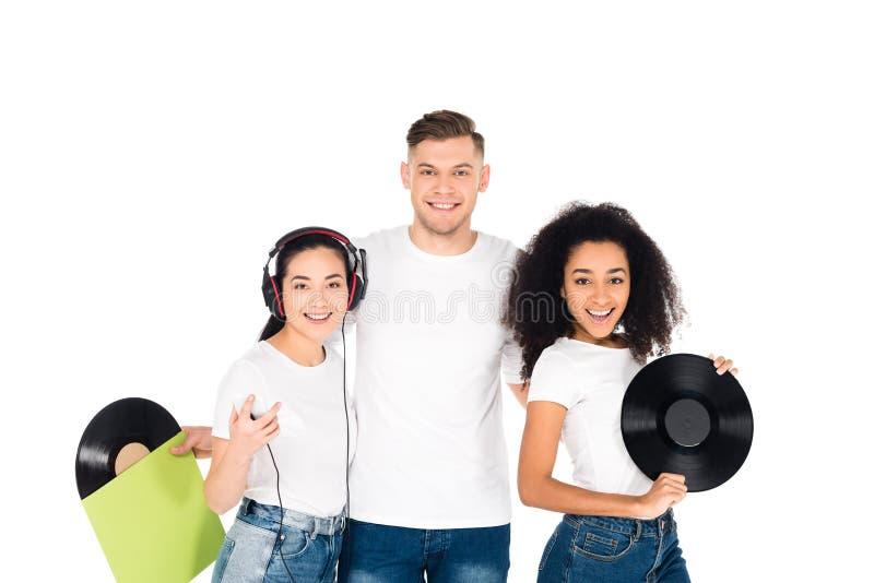 jovens multiculturais que abraçam e que mantêm registros de vinil isolados imagem de stock