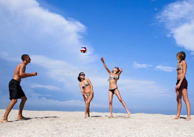 Jovens na praia que joga o voleibol foto de stock