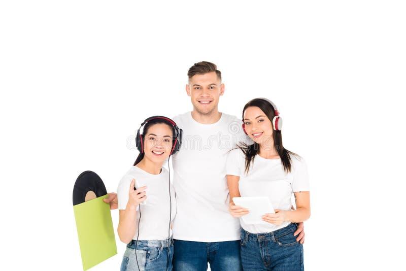 jovens nos fones de ouvido que abraçam e que mantêm o registro de vinil e a tabuleta digital isolados fotografia de stock