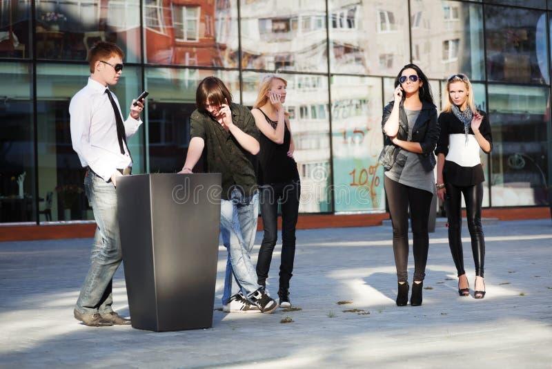 Jovens nos telefones móveis imagens de stock