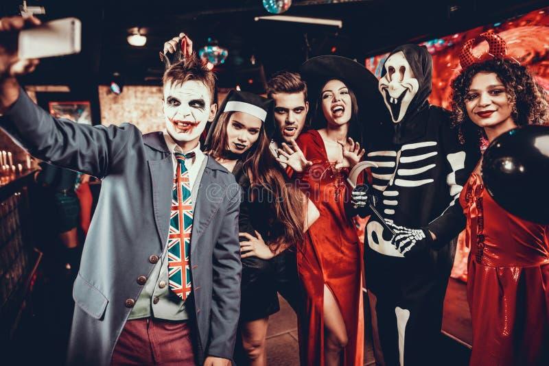 Jovens nos trajes de Dia das Bruxas que tomam Selfie imagens de stock royalty free