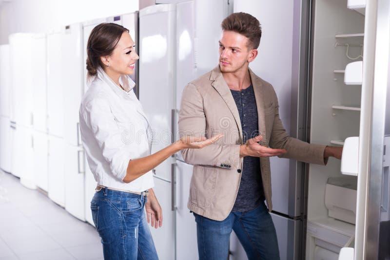 Jovens que admiram os pares que escolhem o refrigerador novo no hipermercado imagem de stock royalty free