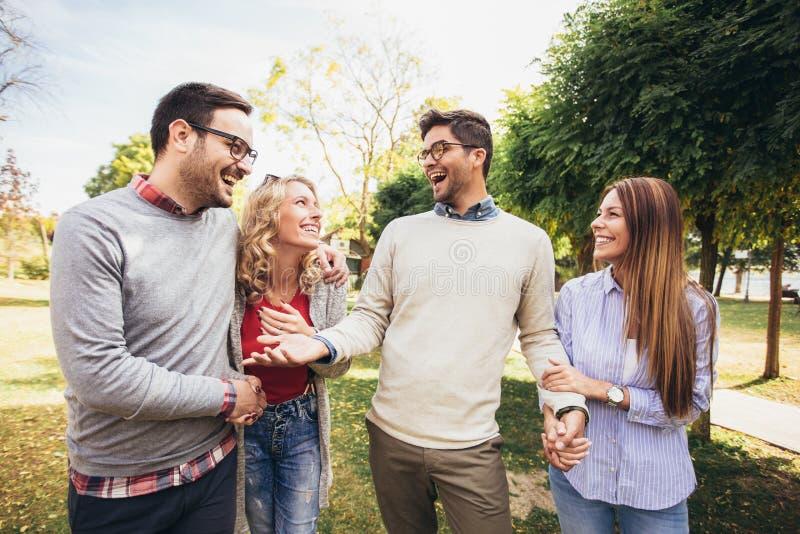 Jovens que andam através do parque Amigos que têm o divertimento exterior imagens de stock royalty free