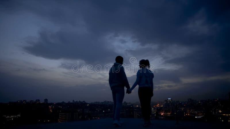 Jovens que apreciam a noite romântica no telhado, cidade iluminada na noite foto de stock