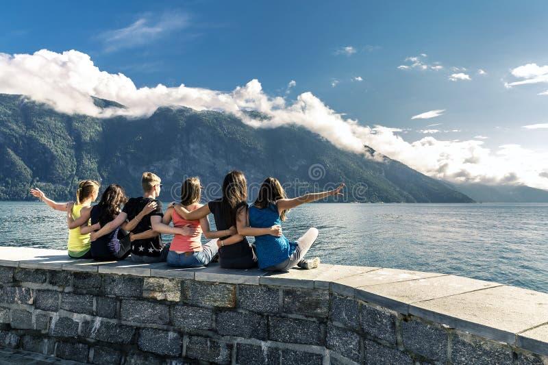 Jovens que apreciam o dia ensolarado no fiorde, Noruega imagem de stock royalty free