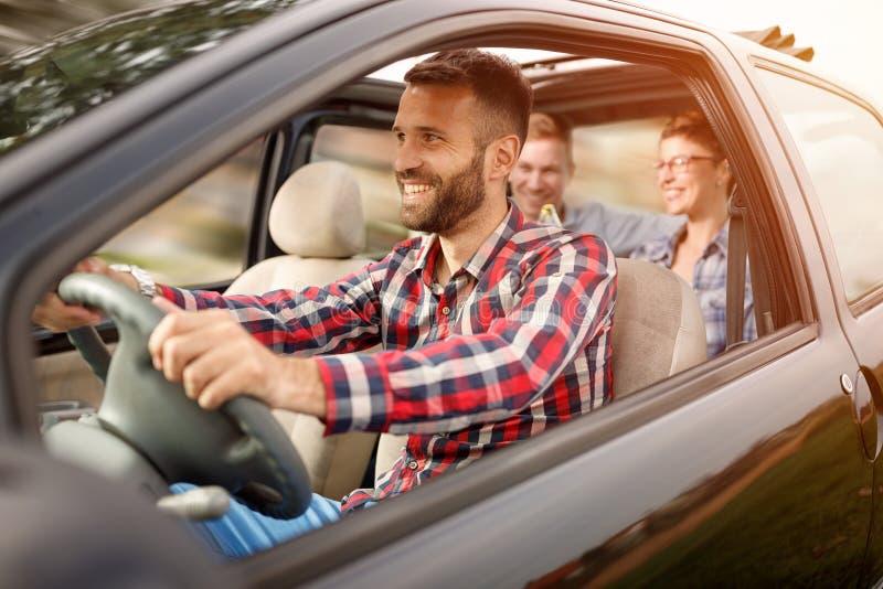 Jovens que apreciam uma viagem por estrada no carro imagens de stock