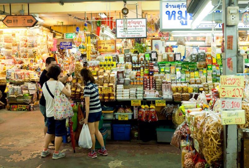 Jovens que compram o alimento exótico no mercado com especiarias, carne, os legumes frescos e os doces fotografia de stock